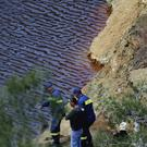 Firefighters and investigators search the man-made lake near the village of Mitsero outside of the capital Nicosia (Petros Karadjias/AP)
