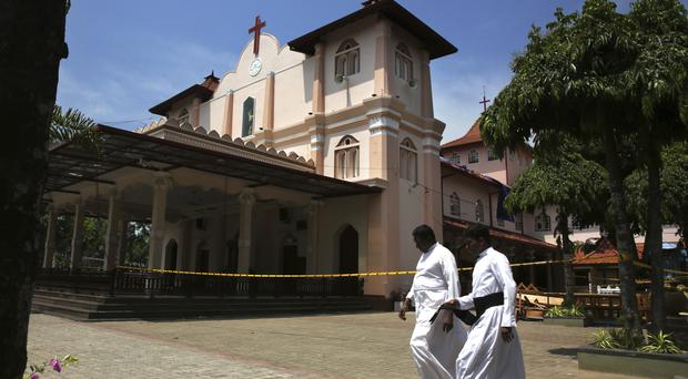 Catholic priests walk outside St Sebastian's Church which was targeted by bombers (Manish Swarup/AP)