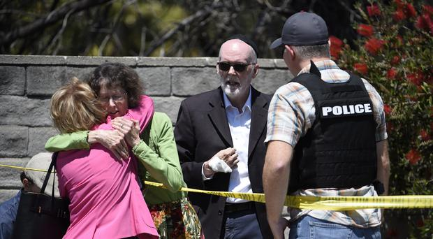 Two people hug as another talks to a San Diego County Sheriff's deputy outside of the Chabad of Poway Synagogue (Denis Poroy/AP)
