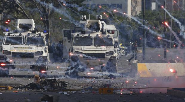 Fireworks launched by opponents of Venezuela's President Nicolas Maduro land near Bolivarian National Guard armoured vehicles loyal to Maduro (Ariana Cubillos/AP)