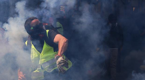A man wearing a yellow stands amidst tear gas during a May Day demonstration in Paris (Francois Mori/AP)
