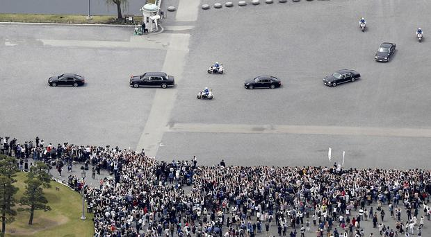 The motorcade of Japan's new Emperor Naruhito, second from left, moves past well-wishers (Takuya Inaba/AP)
