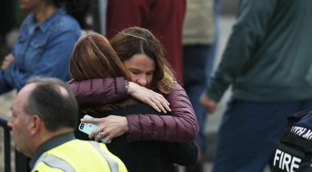 Parents hug as they wait for their children at the recreation centre where students were reunited with their parents after a shooting (David Zalubowski/AP)