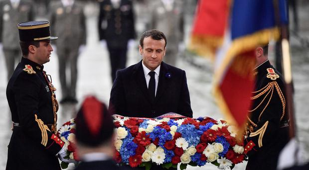 French president Emmanuel Macron lays a wreath of flowers at the Tomb of the Unknown Soldier under the Arc de Triomphe (Martin Bureau, Pool via AP)