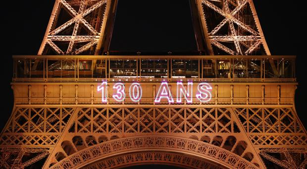 A light show illuminates the Eiffel Tower on its 130th anniversary (Christophe Ena/AP)