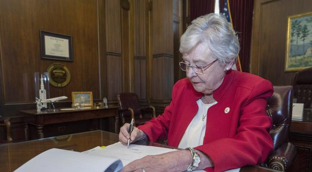 Alabama Governor Kay Ivey signs a bill that virtually outlaws abortion in the state (Hal Yeager/Alabama Governor's Office/AP)