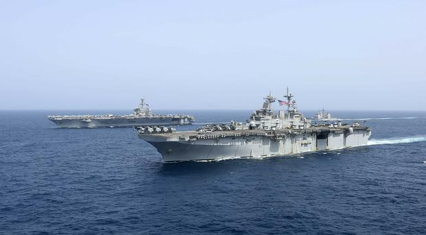 USS Kearsarge sails in front of the USS Abraham Lincoln in the Arabian Sea (US Navy via AP)
