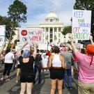 Protesters for women's rights hold a rally on the Alabama Capitol steps (AP)