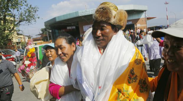 Kami Rita is welcomed by his wife at the airport in Kathmandu (Niranjan Shrestha/AP)