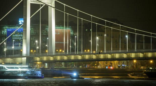 A rescue boat searches for victims after a tourist boat crashed with a river cruise boat, in River Danube in Budapest (Peter Lakatos/MTI via AP)
