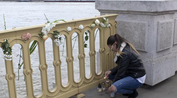 A woman lights a candle at the Margit bridge on the Danube (Marko Drobnjakovic/AP)