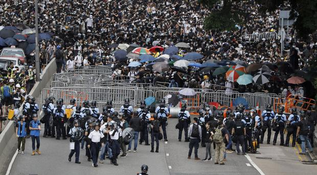 Policemen in anti-riot gear stand guard against the protesters on a closed-off road near the Legislative Council in Hong Kong (AP Photo/Vincent Yu)