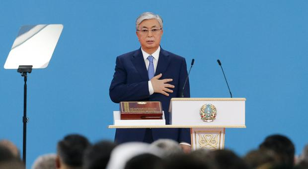 Kassym-Jomart Tokayev puts his hand on heart as he takes the oath of office (Alexei Filippov/AP)