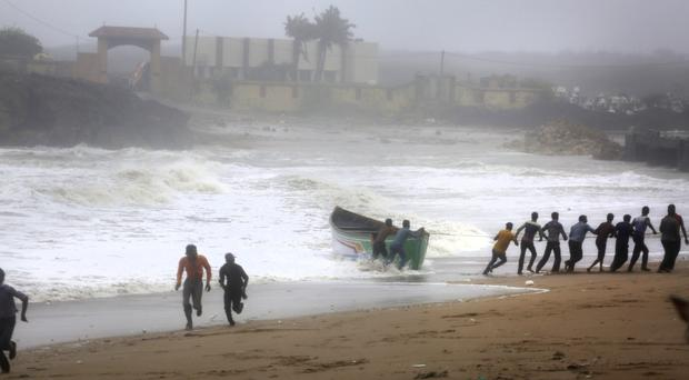 People try to pull back a fishing boat that was carried away by waves on the Arabian Sea coast as others run to take shelter in Veraval, Gujarat, India (Ajit Solanki/AP)
