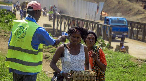People crossing the border have their temperature taken to check for symptoms of Ebola (Al-hadji Kudra Maliro/AP)