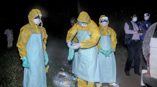 Workers wearing protective clothing prepare to bury an ebola victim in Uganda (Ronald Kabuubi/AP)