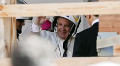 Pope Francis wears a safety helmet as he visits the earthquake damaged cathedral of Camerino (Gregorio Borgia/AP)