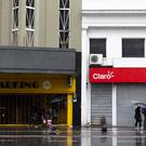 People walk in front of closed stores during the blackout in Buenos Aires (Tomas F Cuesta/AP)