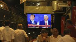 People watch a live broadcast of a televised debate between Istanbul's mayoral candidate Binali Yildirim, right, of Turkey's ruling Justice and Development Party, or AKP, and Ekrem Imamoglu, left, candidate of the secular opposition Republican People's Party (Emrah Gurel/AP)
