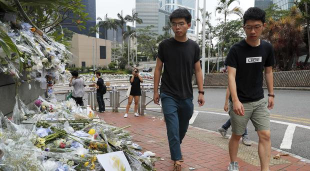 Pro-democracy activist Joshua Wong, left, is accompanied by Nathan Law as they arrive at a makeshift memorial in Hong Kong to pay respects to a protester who fell to his death (Kin Cheung/AP)