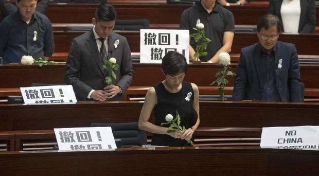 Pro-democracy legislators pay a silent tribute to a protester who fell to his death at the weekend (AP)