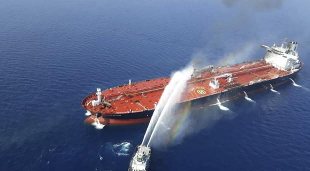 An Iranian navy boat sprays water to extinguish a fire on an oil tanker in the sea of Oman (Tasnim News Agency/AP)