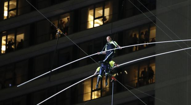 Aerialist Nik Wallenda, top, steps over his sister Lijana as they walk on a high wire above Times Square (AP Photo/Jason Szenes)