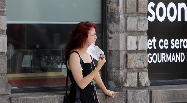 A woman uses paper as a fan in Lille, northern France (Michel Spingler/AP)