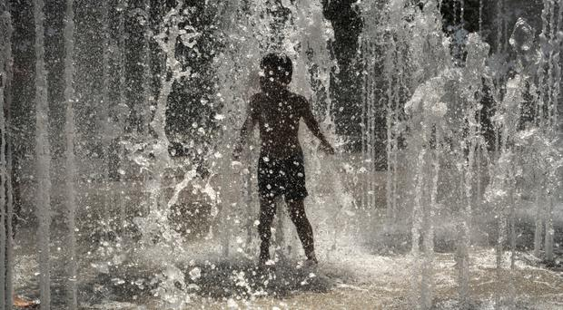 Children play in a fountain in Lyon, central France (Laurent Cipriani/AP)