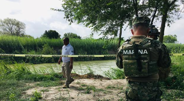 Mexican authorities walk along the Rio Grande bank where the bodies were found (AP Photo/Julia Le Duc)