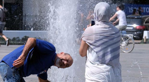 A man cools off at a fountain in Turin in Italy (Alessandro Di Marco/ANSA via AP)