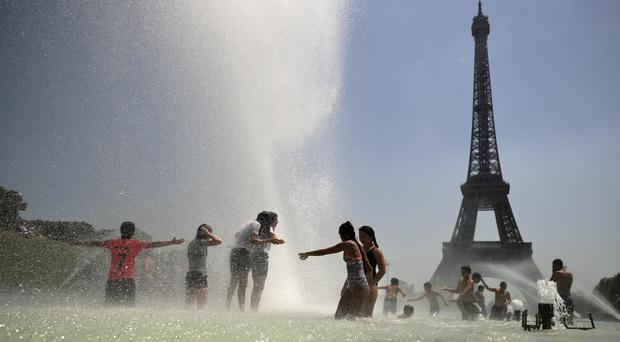 Youngsters cool off at the Trocadero public fountain in Paris (Francisco Seco/AP)