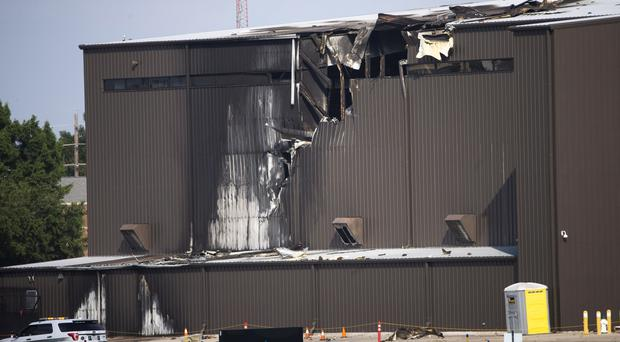 Damage is seen to a hangar after a twin-engine plane crashed into the building (Shaban Athuman/AP)