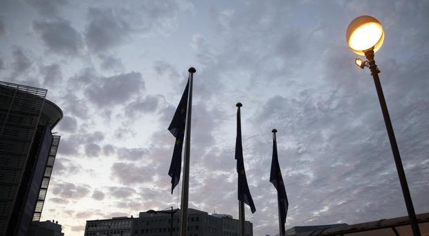 European Union flags flap in the wind as the sun rises during an all night negotiating session (Virginia Mayo/AP)