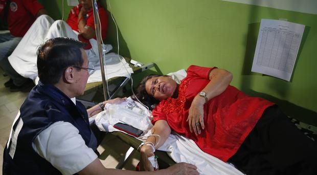 Philippine Health Secretary Francisco Duque III talks to patients who fell ill during the 90th birthday celebration of former Philippine First Lady Imelda Marcos (Bullit Marquez/AP)