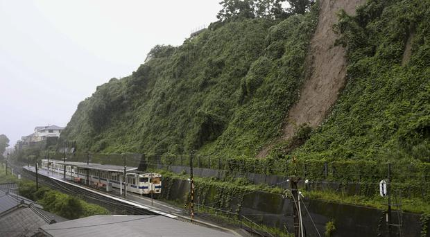 A landslide due to heavy rain is seen near a train station in Kagoshima City, Japan (Kyodo News via AP)