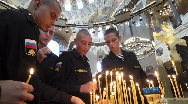 Russian sailors light candles during a service to commemorate the crew members that were killed (Dmitri Lovetsky/AP)
