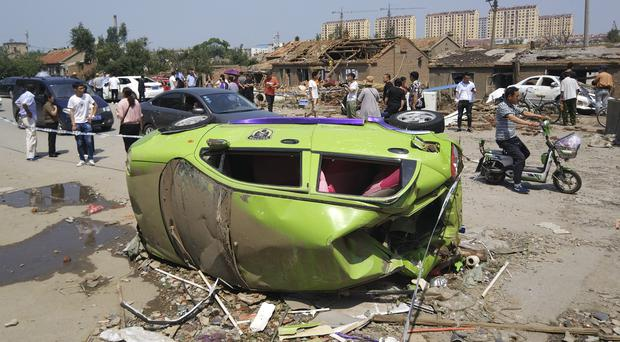 Residents pass an overturned car in the aftermath of a tornado in China (Chinatopix Via AP)