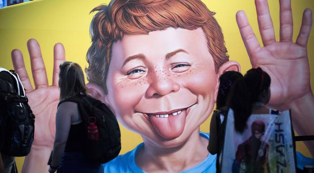 The face of Alfred E. Neuman is framed by attendees at the DC booth during the first day of Comic-Con International (Kevin Sullivan/AP)