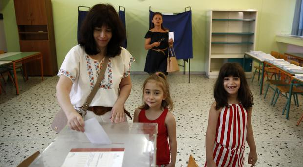 A woman casts her ballot with her daughters at a polling station in Athens (AP Photo/Thanassis Stavrakis)