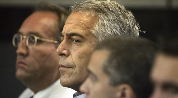 Jeffrey Epstein, centre, in custody in West Palm Beach (Uma Sanghvi/Palm Beach Post/AP)