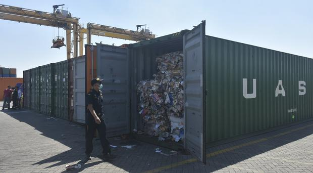 Indonesian custom officers open containers full of waste (AP)