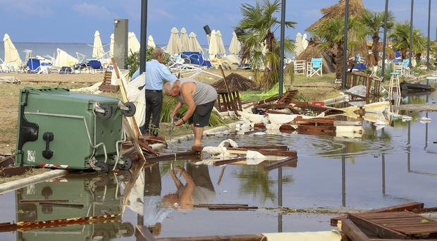 Two men search debris after a storm at Nea Plagia village in Halkidiki region (Giannis Moisiadis/InTime News via AP)