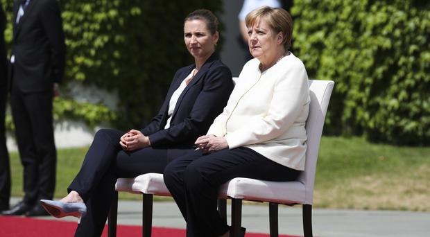 German Chancellor Angela Merkel, right, and Danish Prime Minister Mette Frederiksen sit on chairs as they listen to the national anthems (Markus Schreiber/AP)