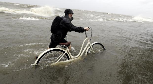 Tyler Holland guides his bike through the water as winds from Tropical Storm Barry push water from Lake Pontchartrain (David J Phillip/AP)