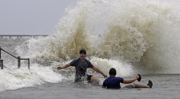 Tyler Cancienne, left, and Jacob LeBlanc are pushed over by waves as winds from Tropical Storm Barry push water from Lake Pontchartrain over the seawall (David J Phillip/AP)