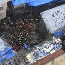 Rescuers work at the site of a building that collapsed in Mumbai (Rajanish Kakade/AP)