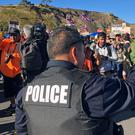 A police officer gestures at demonstrators blocking a road at the base of Hawaii's tallest mountain, who are protesting the construction of a giant telescope (Caleb Jones/AP)