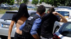 The suspects cover their faces with their shirts as they arrive at the courthouse in Paralamni (Petros Karadjias/AP)