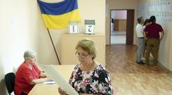 A woman holds a ballot at a polling station during a parliamentary election in Kiev, Ukraine (Evgeniy Maloletka/AP)